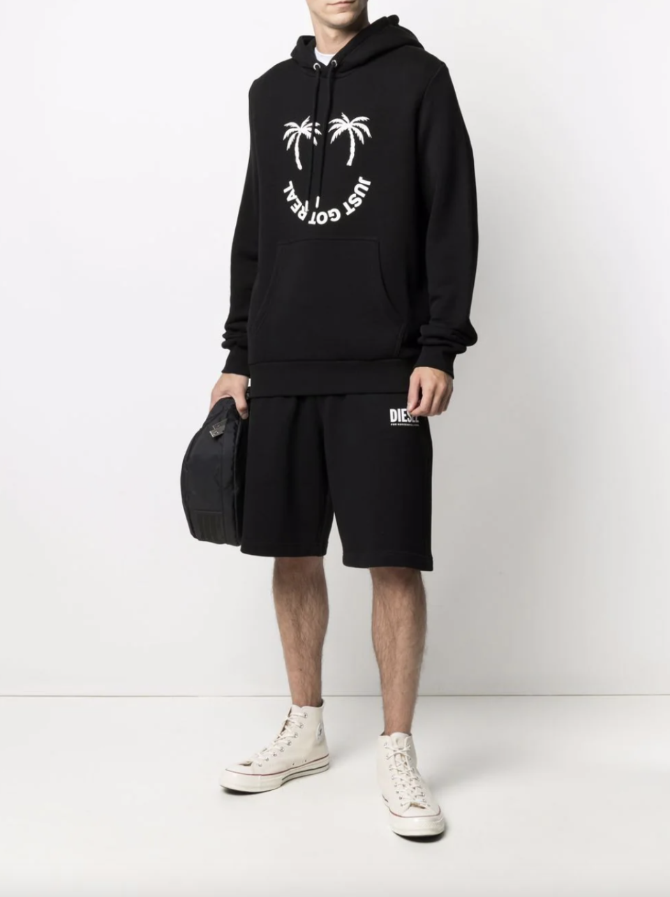 model in black Diesel Green Label Pal-Print Hoodie with palm trees and black shorts