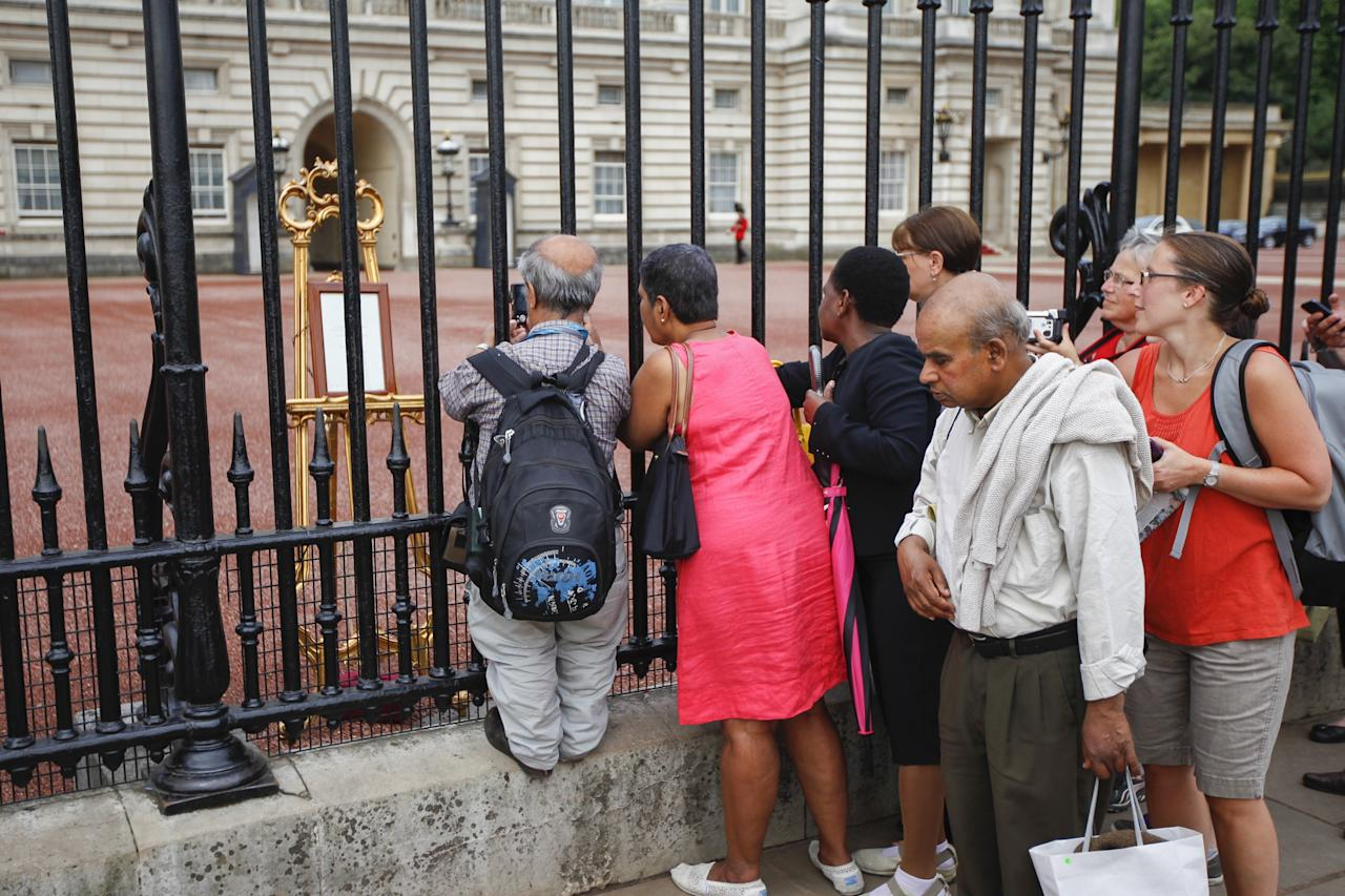 LONDON, ENGLAND - JULY 23: Crowds gather outside Buckingham Palace to read the easel displaying the announcement of the son of The Duke and Duchess of Cambridge on July 23, 2013 in London, England. The Duchess of Cambridge yesterday gave birth to a boy at 16.24 BST and weighing 8lb 6oz, with Prince William at her side. The baby, as yet unnamed, is third in line to the throne and becomes the Prince of Cambridge. (Photo by Dan Dennison/Getty Images)