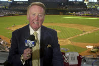 FILE - In this July 3, 2002, file photo, Los Angeles Dodgers television play-by-play announcer Vin Scully rehearses before a baseball game between the Dodgers and the Arizona Diamondbacks in Phoenix. To baseball fans, opening day is an annual rite of springthat evokes great anticipation and warm memories. This year's season was scheduled to begin Thursday, March 26, 2020, but there will be no games for a while because of the coronavirus outbreak. (AP Photo/Paul Connors, File)
