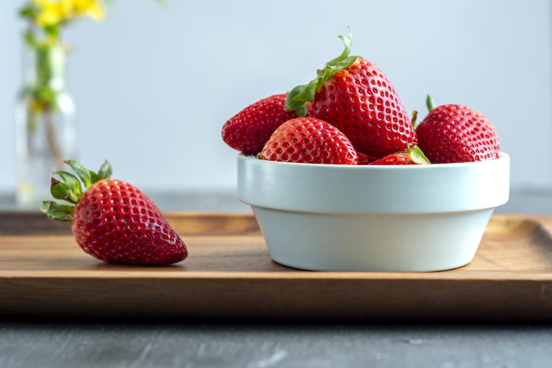Small bowl filled with whole ripe strawberries sitting on a wooden serving tray with a single strawberry on the board. Gray background with a vase and yellow flower in the background.