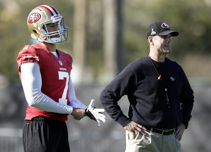 San Francisco 49ers quarterback Colin Kaepernick (7) pulls on a glove as he stands with head coach Jim Harbaugh during practice on Thursday, Jan. 31, 2013, in New Orleans. The 49ers are scheduled to play the Baltimore Ravens in the NFL Super Bowl XLVII football game on Feb. 3. (AP Photo/Mark Humphrey)