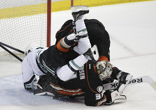 Dallas Stars' Alex Goligoski, top left, and Anaheim Ducks' Ben Lovejoy stumble over Anaheim Ducks goalie Frederik Andersen, of Denmark, in the first period of Game 5 of the first-round NHL hockey Stanley Cup playoff series on Friday, April 25, 2014, in Anaheim, Calif. (AP Photo/Jae C. Hong)