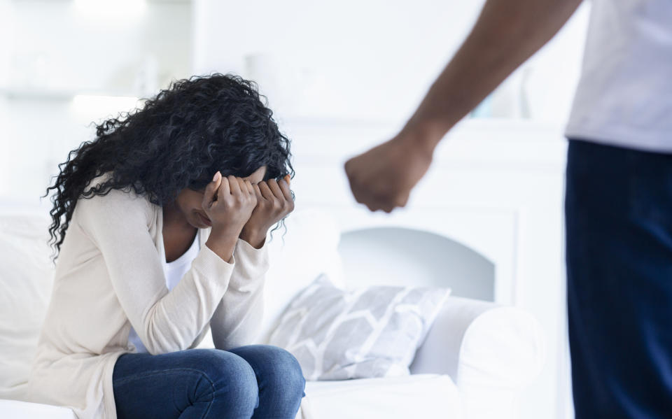 Domestic abuse. Young woman suffering from home violence, hiding her face from husband's fist.