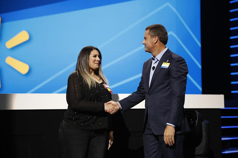 Doug McMillon President and CEO Walmart Inc. presents a promotion to Shabnam Ighani at the 2019 Walmart Shareholders June 7, 2019 in Bud Walton Arena, Fayetteville, Arkansas.