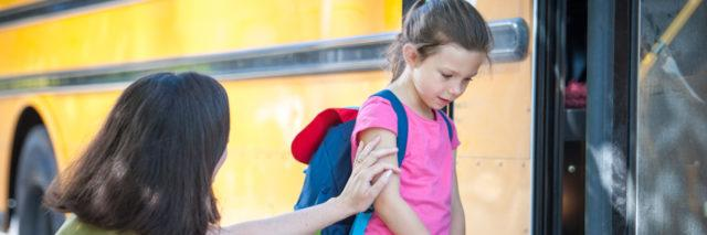 Girl sad and being comforted as she gets on the school bus.