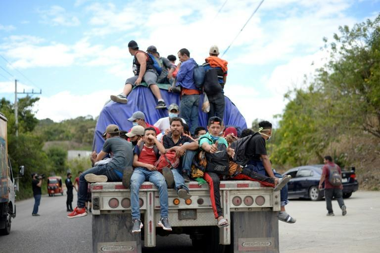 Honduran migrants, part of a caravan seeking to reach the United States, get a ride on a truck in Camotan, Guatemala on January 16, 2021