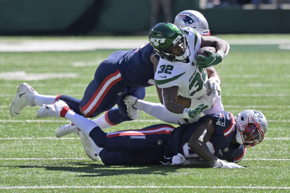 New York Jets running back Michael Carter, center, is brought down by New England Patriots defenders during the first half of an NFL football game, Sunday, Sept. 19, 2021, in East Rutherford, N.J. (AP Photo/Bill Kostroun)
