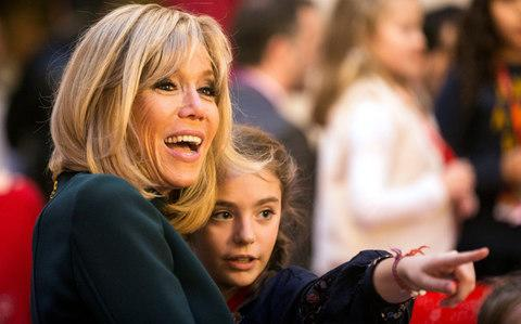 Brigitte Macron, wife of the French President, reacts with a young girl during the Christmas party for children at the Elysee Palace in Paris - Credit:  REUTERS