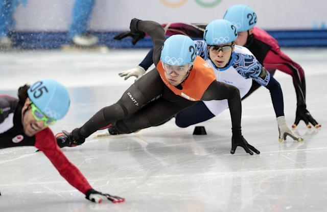 Charles Hamelin of Canada, front left, crashes out ahead of Sjinkie Knegt of Netherlands, second from left, Semen Elistratov of Russia, second from right, and Robert Seifert of Germany as they compete in a men's 500m short track speedskating heat at the Iceberg Skating Palace during the 2014 Winter Olympics, Tuesday, Feb. 18, 2014, in Sochi, Russia. (AP Photo/Ivan Sekretarev)