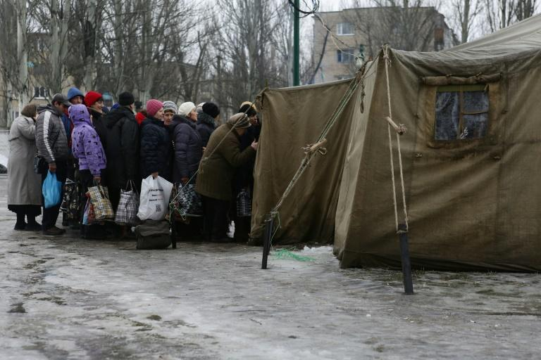 Residents of the war-scarred and cashed-starved Ukraine queue outside a tent to get warm clothes in Avdiivka, Donetsk region, on February 5, 2017