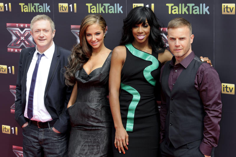 From left, Irish pop impresario Louis Walsh, British singer Tulisa Contostavlos, U.S. singer Kelly Rowland and British singer Gary Barlow, pose for photographers at the press launch, for the British version of X Factor at a central London venue, Wednesday, Aug. 17, 2011. (AP Photo/Jonathan Short)