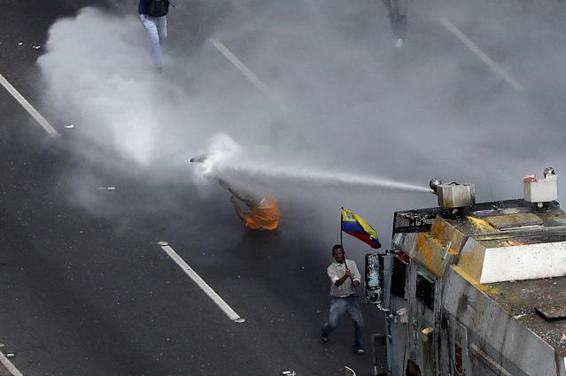 <p>Opposition Deputy Carlos Paparoni is hit by a jet of water during clashes at a march to the state ombudsman's office in Caracas, Venezuela, May 29, 2017. (Carlos Garcia Rawlins/Reuters) </p>