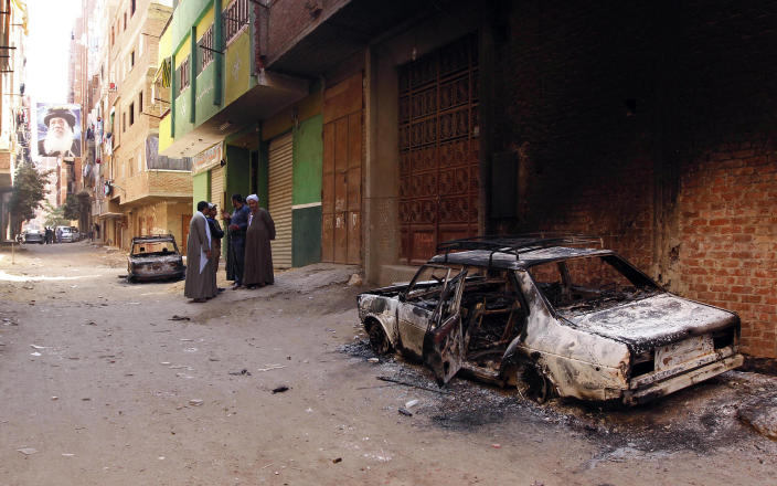 Several burned cars belonging to Egyptian Christians remain in the street after clashes between Muslims and Christians in Qalubiya, just outside Cairo, Egypt, Saturday, April 6, 2013. Several Egyptians including 4 Christians and a Muslim were killed in sectarian clashes before dawn on Saturday, security officials said. A picture of the late Coptic Pope Shenouda is seen at end of street. (AP Photo/Mohammed Nouhan, El Shorouk Newspaper) EGYPT OUT