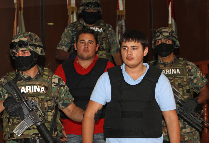 "Mexican marines escort aJesus Alfredo Guzman Salazar, 26, in the back with red T-shirt, and Kevin Beltran Rios, during their presentation to the media in Mexico City, Thursday, June 21, 2012. Mexican marines detained Jesus Alfredo Guzman Salazar, 26, who is allegedly one of the sons of Mexico's most-wanted drug kingpin, Joaquin ""El Chapo"" Guzman Loera, leader of the powerful Sinaloa cartel, and his alleged accomplice Beltran Rios in the western state of Jalisco thanks to intelligence work, the Navy said in a brief statement. (AP Photo/Eduardo Verdugo)"