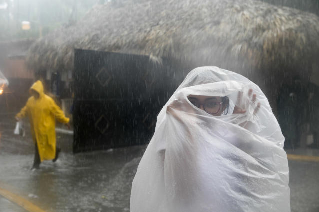 <p>A woman covers herself with a plastic bag as she makes her way to work as Hurricane Maria approaches the coast of Bavaro, Dominican Republic, Wednesday, Sept. 20, 2017. (Photo: Tatiana Fernandez/AP) </p>