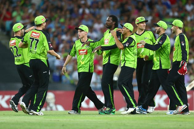 Chris Gayle of the Thunder is congratulated by his team after taking the wicket of Brad Haddin of the Sixers during the Big Bash League match between Sydney Thunder and the Sydney Sixers at ANZ Stadium on December 30, 2012 in Sydney, Australia.  (Photo by Mark Kolbe/Getty Images)