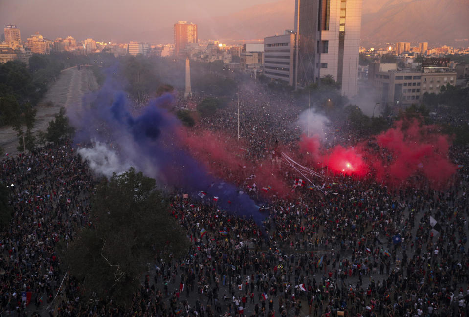 Clouds of smoke from flares hover over a group of anti-government protesters gathered in the Plaza Italia, in Santiago, Chile, Friday, Nov. 8, 2019. Chile's unrest began last month over a subway fare hike. But it has morphed into a movement demanding a broad range of changes. (AP Photo/Esteban Felix)