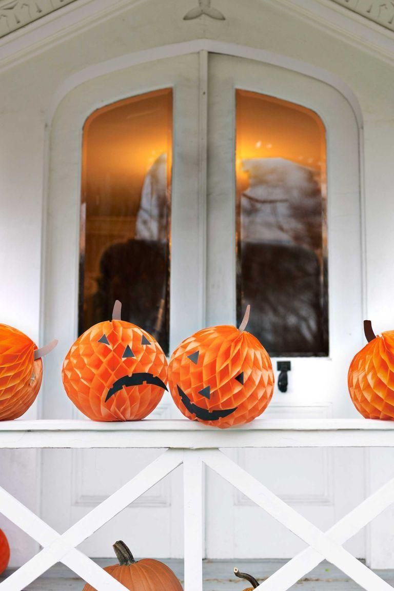 <p>If you're not so crafty with real pumpkins, make some fake ones with tissue paper balls. All you need to do is cut facial features out of black construction paper and glue them on. Keep them under the hood of your porch or hang them in trees on Halloween night (you don't want them to get ruined in the rain). </p>