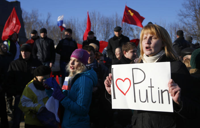 """A pro Russian resident rallies with others at a central square in Donetsk, Ukraine, Friday, March 7, 2014. Russia rallied support Friday for a Crimean bid to secede from Ukraine, with Russia's top lawmaker assuring her Crimean counterpart that the region would be welcomed as """"an absolutely equal subject of the Russian Federation."""" (AP Photo/Sergei Grits)"""