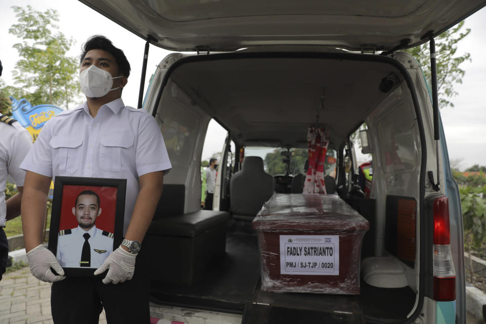 A colleague holds a portrait of Fadly Satrianto, a victim of the crash of Sriwijaya Air flight SJ-182 during his funeral in Surabaya, East Java, Indonesia, Friday, jan. 15, 2021. More searchers and rescuers joined the search Friday for wreckage and victims from the Indonesian plane that crashed last weekend in the Java Sea. (AP Photo/Trisnadi)