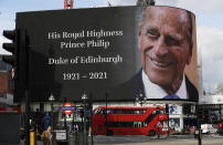 FILE - In this file photo dated Friday, April 9, 2021, a tribute to Britain's Prince Philip is projected onto a large screen at Piccadilly Circus in central London. Buckingham Palace officials say Prince Philip, the husband of Queen Elizabeth II, has died, aged 99. Prince Philip who died Friday April 9, 2021, aged 99, lived through a tumultuous century of war and upheavals, but he helped forge a period of stability for the British monarchy under his wife, Queen Elizabeth II. (AP Photo/Matt Dunham, FILE)