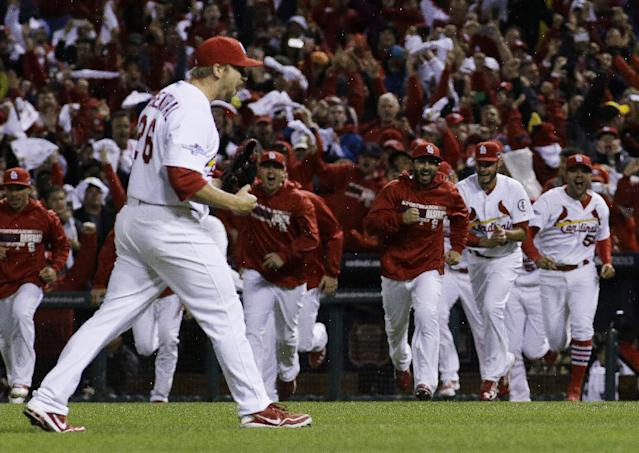 The St. Louis Cardinals bench erupts after Game 6 of the National League baseball championship series against the Los Angeles Dodgers, Friday, Oct. 18, 2013, in St. Louis. The Cardinals won 9-0 to win the series. (AP Photo/David J. Phillip)