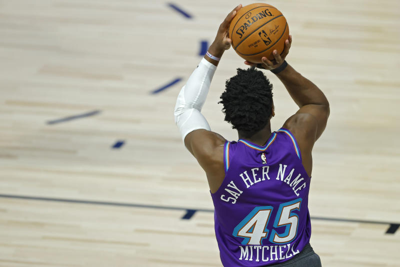 "Donovan Mitchell shoots a basketball wearing his ""Say Her Name"" jersey."