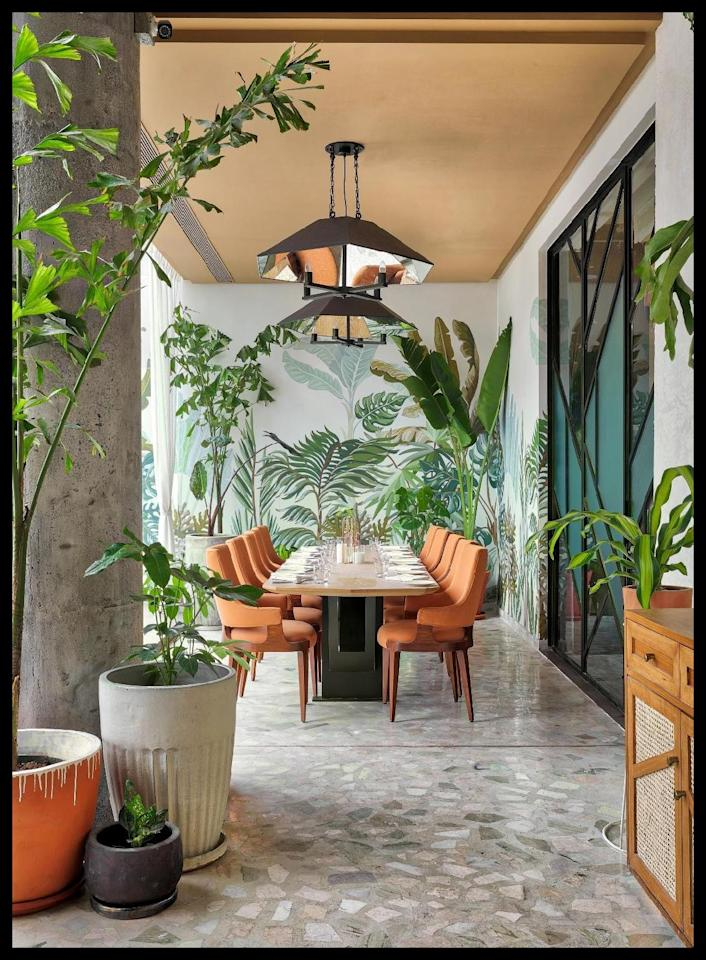 At Ishaara, a sign-and-dine restaurant in Mumbai, interior designer Minnie Bhatt created conservatory-themed interiors. Real-life potted plants echo those featured on the custom-printed wallpaper, rendering a three-dimensional effect. Click on to see how you can add some monstera magic to your space. <em>Photo Courtesy: Minnie Bhatt for Ishaara</em>