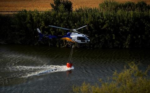 A helicopter refills its water bucket in the river to extinguish a wildfire near the city of Toledo - Credit: Reuters