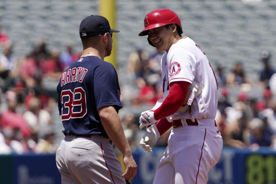 Los Angeles Angels' Shohei Ohtani, right, talks with Boston Red Sox second baseman Christian Arroyo after Ohtani hit a single and then advanced to second during the first inning of a baseball game Wednesday, July 7, 2021, in Anaheim, Calif. (AP Photo/Mark J. Terrill)