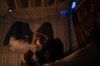 Mohamed, 19, from Morocco, smokes a hookah, also known as Arjilah or Shisha in his tent in San Cristobal de la Laguna, in the Canary Island of Tenerife, Spain, Saturday, March 20, 2021. While Spain has been critical of its European neighbours' lack of solidarity when it comes to sharing the responsibility of migration, the country is similarly being criticized by migrants, authorities and human rights organizations on the Canary Islands where some 23,000 people arrived by sea last year and where many thousands remain on the island forcefully. (AP Photo/Joan Mateu)