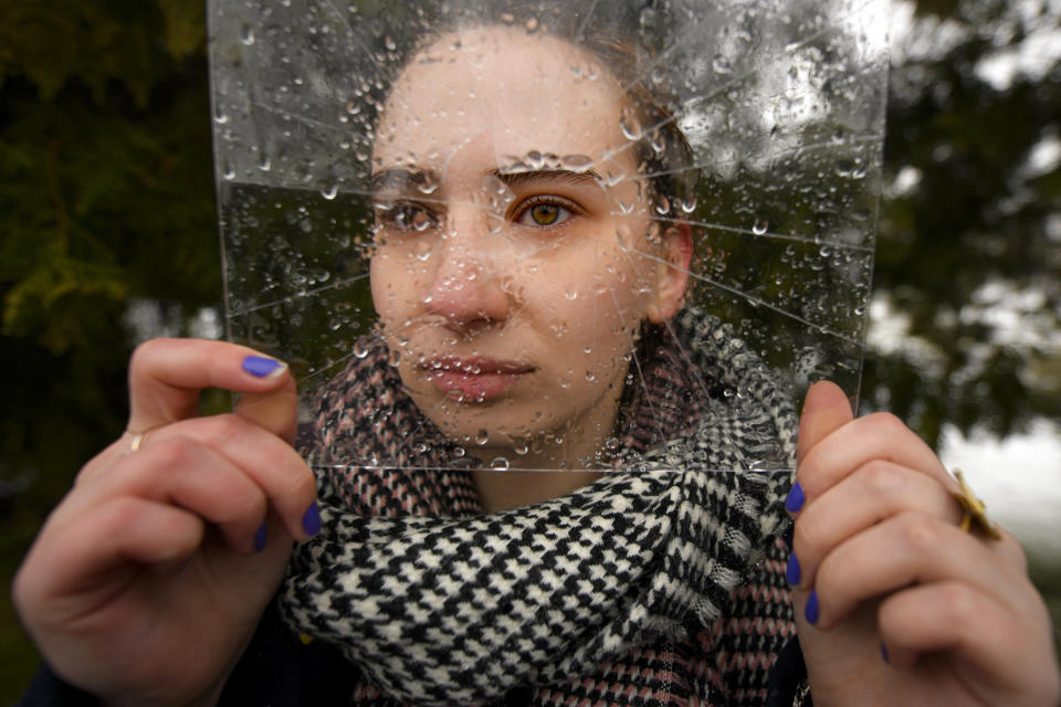 A woman poses holding a piece of cracked plastic sheet during a flashmob to raise awareness of the increased levels of violence against women since the COVID-19 pandemic started one year ago, in Bucharest, Romania, Wednesday, March 10, 2021. Participants called for a bill, currently blocked in procedures in Romania's parliament, that would require men who are subjects of restrictive orders to wear ankle monitors, to be voted into law. (AP Photo/Andreea Alexandru)