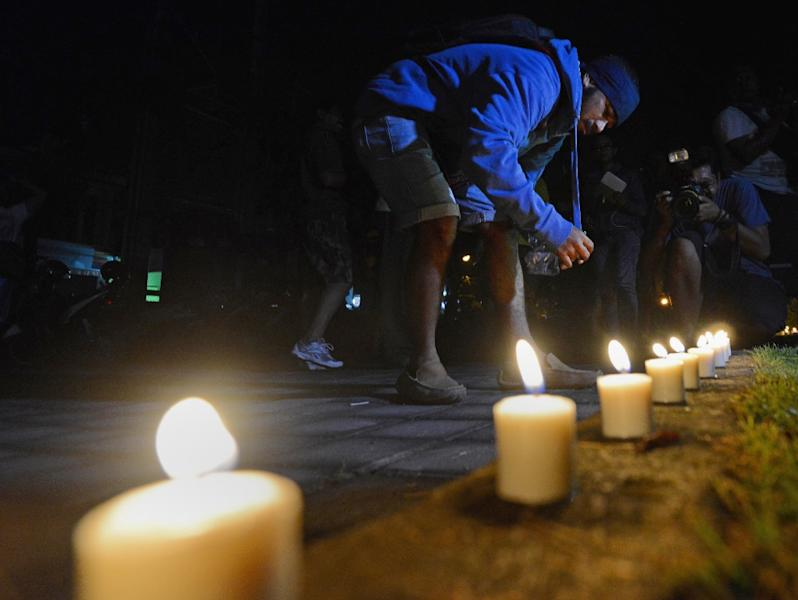 A supporter of two Australian drug smugglers on death row lights candles for a vigil outside Kerobokan prison on Bali island on March 4, 2015 as authorities transported the men to another a high-security prison off Java island (AFP Photo/Sonny Tumbelaka)