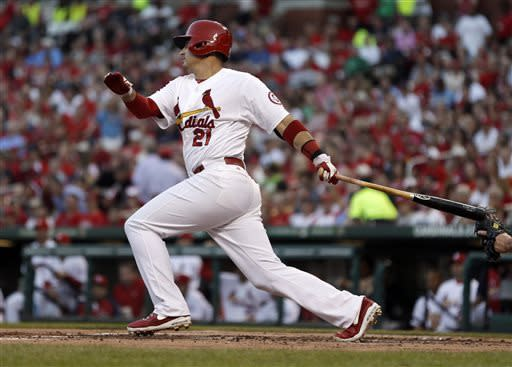 St. Louis Cardinals' Allen Craig follows through on a two-run single during the first inning of a baseball game against the New York Mets on Tuesday, May 14, 2013, in St. Louis. (AP Photo/Jeff Roberson)
