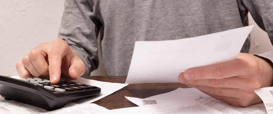 Man hands, a finger on button of calculator with financial documents in a hand and others on the table