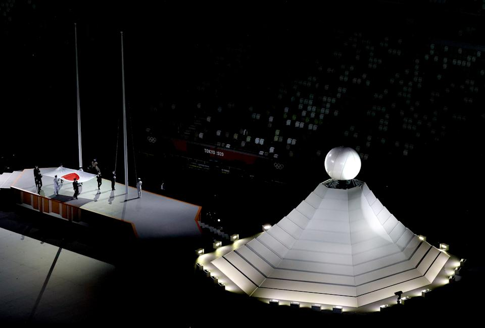 <p>TOKYO, JAPAN - JULY 23: The Japanese flag is carried past the Olympic cauldron during the Opening Ceremony of the Tokyo 2020 Olympic Games at Olympic Stadium on July 23, 2021 in Tokyo, Japan. (Photo by Richard Heathcote/Getty Images)</p>