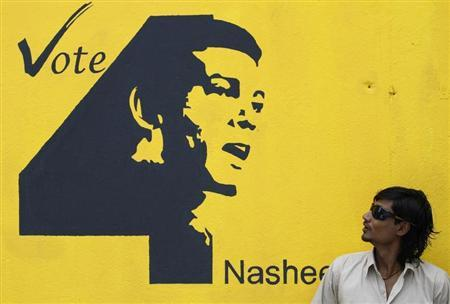 A Maldivian man looks at a presidential election campaign poster of presidential candidate Mohamed Nasheed in Male