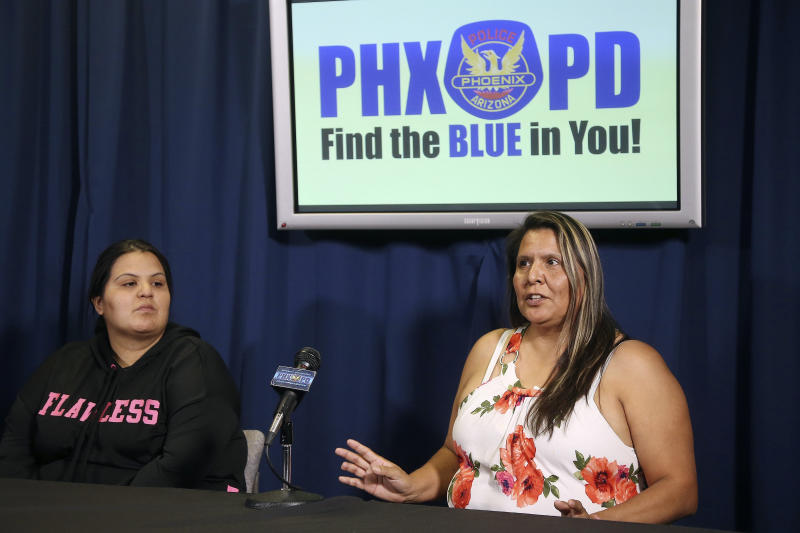 Shannon Vivar, left, listens to her mother Shirley Vivar, right, speak as the two talk about being in their vehicle as they were hit by a red light runner, during a news conference at Phoenix Police headquarters Thursday, Oct. 24, 2019, in Phoenix. Authorities say 28-year-old Ernesto Otanez Oveso is accused of running a red light Oct. 14 in a hit-and-run car crash that nearly struck a couple pushing a stroller across a busy Phoenix street, and remains jailed on suspicion of leaving the scene of a collision and aggravated assault along with a weapons violation, a felony warrant in a probation violation and three misdemeanor warrants. (AP Photo/Ross D. Franklin)