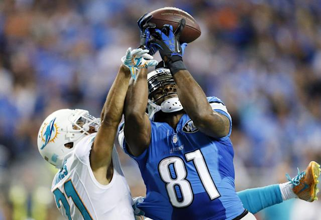 Detroit Lions wide receiver Calvin Johnson (81), defended by Miami Dolphins cornerback Brent Grimes (21), catches 49-yard pass for a touchdown during the first half of an NFL football game in Detroit, Sunday, Nov. 9, 2014. (AP Photo/Rick Osentoski)