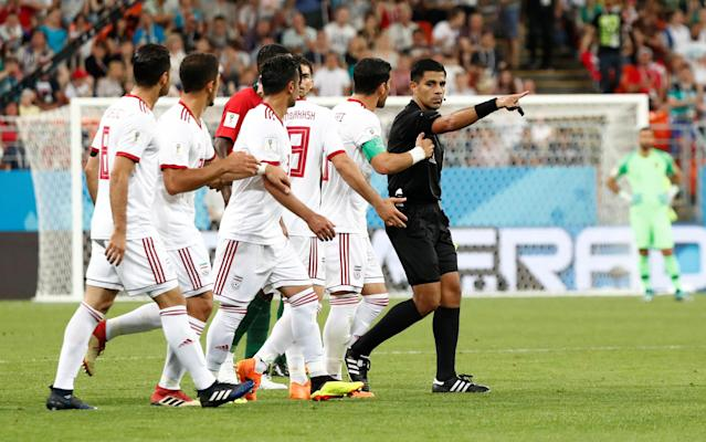 Soccer Football - World Cup - Group B - Iran vs Portugal - Mordovia Arena, Saransk, Russia - June 25, 2018 Referee Enrique Caceres with Iran players as a penalty decision was referred to VAR and a penalty was subsequently awarded after Portugal's Cristiano Ronaldo was fouled in the penalty area by Iran's Saeid Ezatolahi REUTERS/Murad Sezer