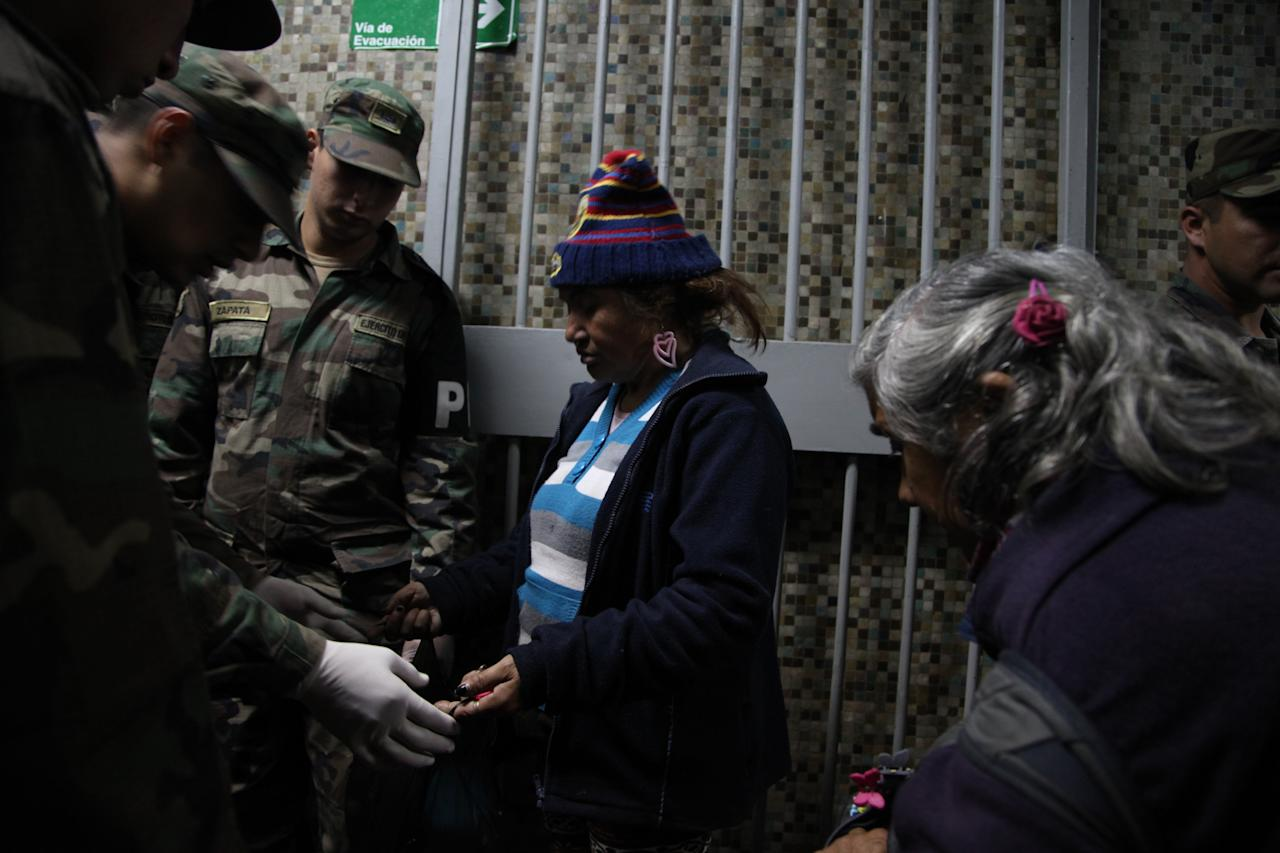 In this May 24, 2013 photo, a woman opens her bag for soldiers to search through before entering a homeless shelter at the indoor stadium Estadio Victor Jara in Santiago, Chile. The stadium, which opened its doors on May 15 as a temporary shelter to house people throughout the winter who normally sleep on the streets, is where Chilean folksinger Victor Jara was tortured and killed in 1973, just days after Chile's bloody 1973 military coup. (AP Photo/Brittany Peterson)