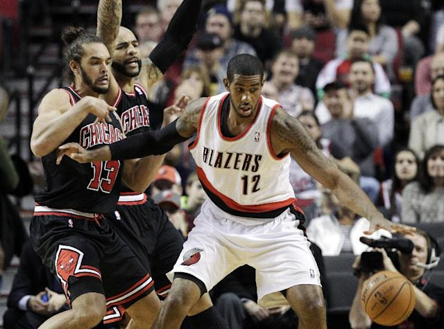 Portland Trail Blazers forward LaMarcus Adridge, right, is double-teamed by the Chicago Bulls' Joakim Noah, left, and Carlos Boozer during the first half of an NBA basketball game in Portland, Ore., Friday, Nov. 22, 2013. (AP Photo/Don Ryan)