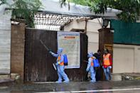 Civic authority workers spray sanitiser on the main door of the residence of Bollywood star Amitabh Bachchan as he tested positive for COVID-19 in Mumbai on July 12, 2020. - Bollywood megastar Amitabh Bachchan, 77, tested positive for COVID-19 on July 11 and was admitted to hospital in Mumbai, with his actor son Abhishek -- who also announced he had the virus -- saying both cases were mild. (Photo by Sujit Jaiswal / AFP)