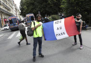"""Two protestors hold the French flag with a message that reads """"no to the pass"""" during a demonstration in Paris, France, Saturday, July 31, 2021. Demonstrators gathered in several cities in France on Saturday to protest against the COVID-19 pass, which grants vaccinated individuals greater ease of access to venues. (AP Photo/Adrienne Surprenant)"""