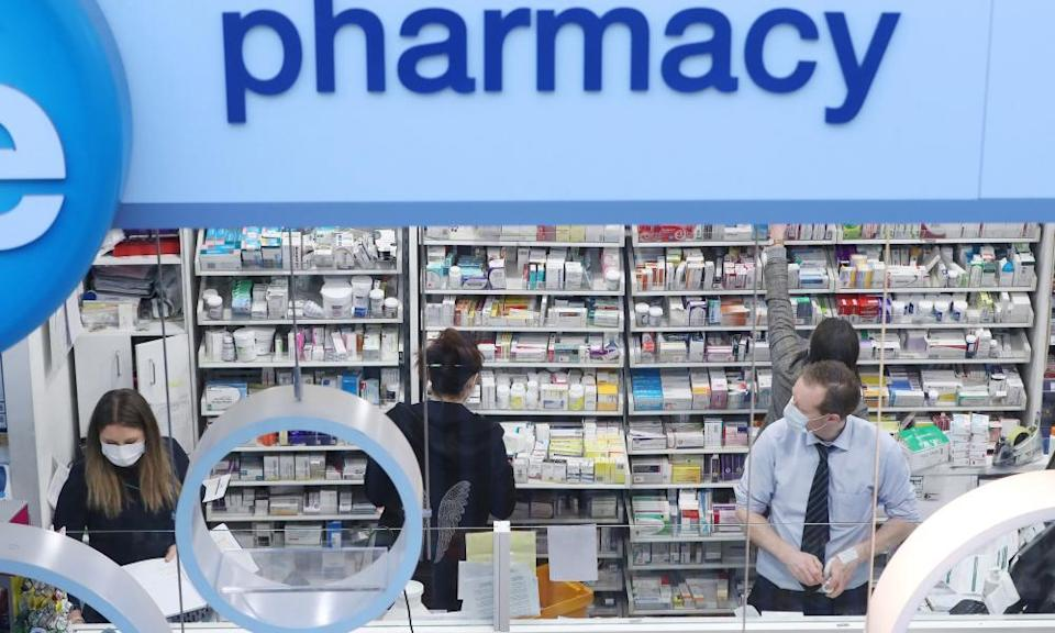 Pharmacists at work behind counter in a shop.
