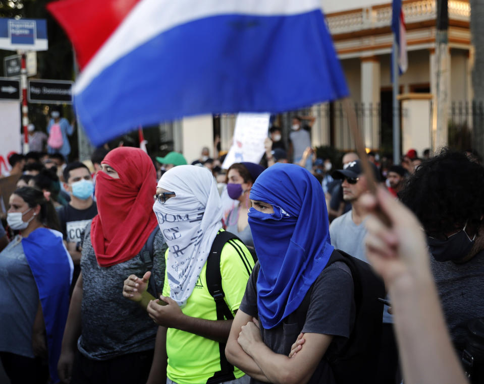 Masked with the colors of the national flag, people protest for the resignation of President Mario Abdo Benitez over his handling of the coronavirus pandemic and the state of the public health system, near his official residence in Asuncion, Paraguay, Sunday, March 7, 2021. (AP Photo/Jorge Saenz)