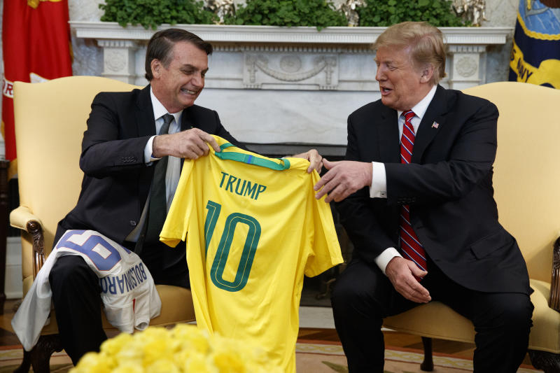 Brazilian President Jair Bolsonaro presents President Donald Trump with a Brazilian national team soccer jersey in the Oval Office of the White House, Tuesday, March 19, 2019, in Washington. (AP Photo/Evan Vucci)