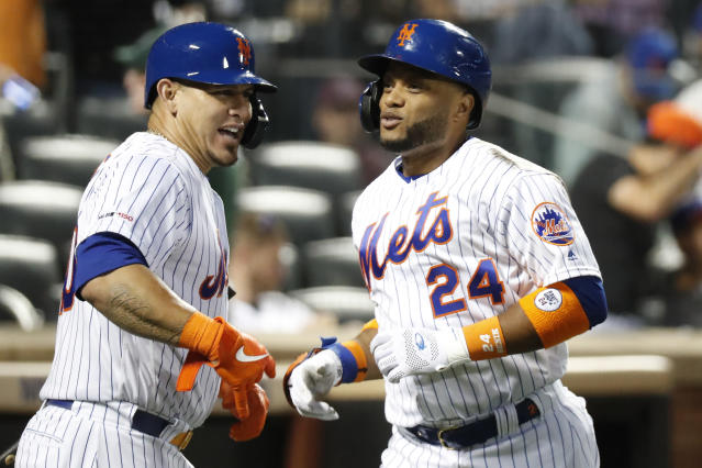 New York Mets' on-deck batter Wilson Ramos, left celebrates with the Mets' Robinson Cano (24) after Cano hit a solo home run during the fourth inning of a baseball game against the San Diego Padres, Tuesday, July 23, 2019, in New York. (AP Photo/Kathy Willens)
