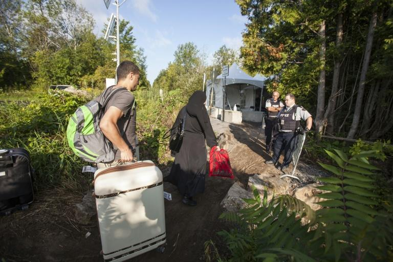Canada announced it will offer permanent resident status to temporary foreign workers, international students and asylum claimants already in Canada, such as the family seen here crossing into Canada from the US in August 2017