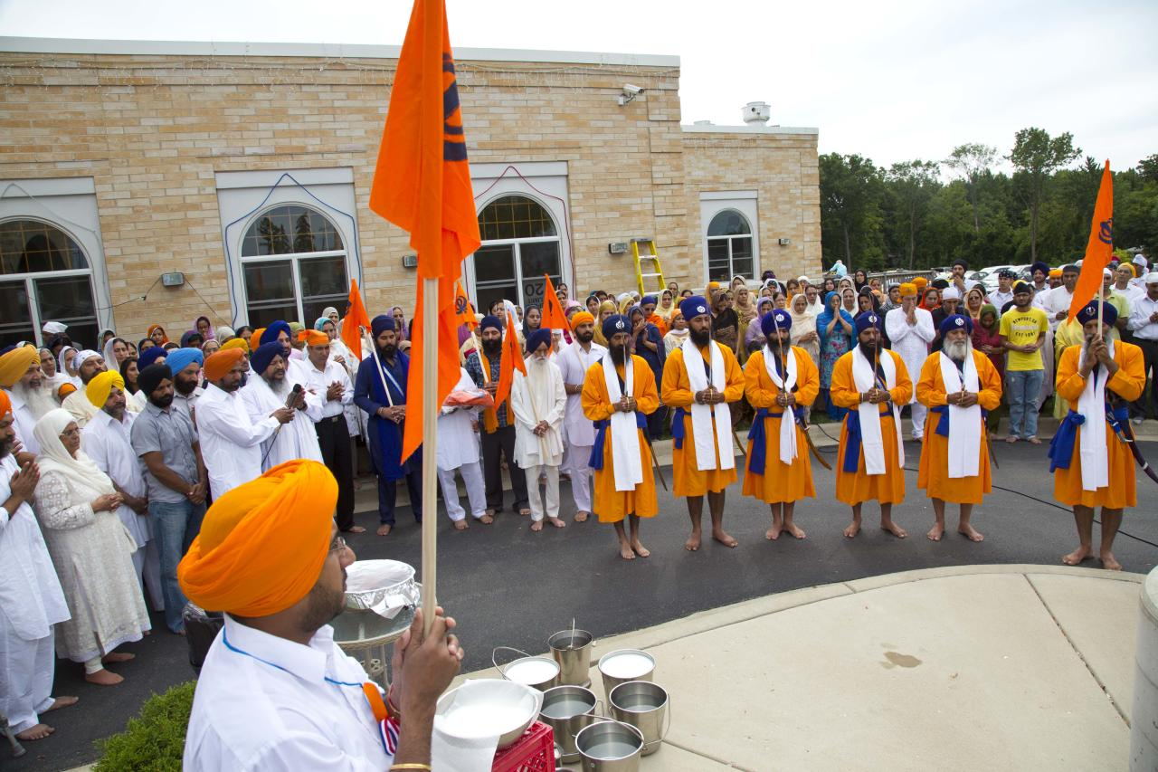 A ceremony of putting the Nishaan Sahib flag to full staff is held outside the Sikh Temple of Wisconsin in Oak Creek, Wis., Sunday, Aug. 12, 2012. More than 100 people gathered for the first Sunday prayer service since a white supremacist shot and killed six people there before fatally shooting himself. (AP Photo/Jeffrey Phelps)
